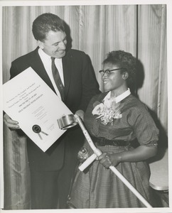 Thumbnail of A man holds the 1960 Thumbs Up Award presented to the Ideal Precision Meter Company with a woman holding a forearm crutch