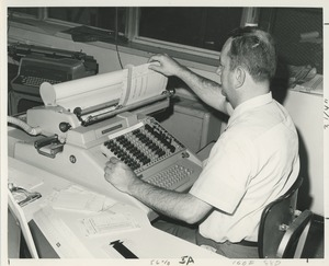 Thumbnail of A man uses a large adding machine at TOWER training