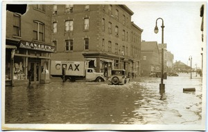 Thumbnail of Aftermath of the great Hartford Flood Automobiles driving on 500 block of flooded Front Street (in front of Kanares Italian          American Grocery)