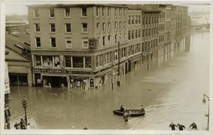 Thumbnail of Aftermath of the great Hartford Flood Flood waters on State Street (Manchester Leaf Tobacco Co. Building to City          Paper Co.) with row boat on the streets and men on roof