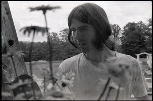 Thumbnail of Bruce Geisler looking at flowers in the garden