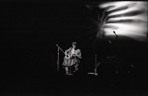 Thumbnail of Taj Mahal in concert at Northfield, Mass.: Taj Mahal seated, playing guitar