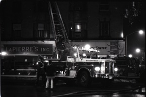 Thumbnail of Fire on Main Street, Greenfield, Mass.: firefighters and firetruck with ladder             extended in front of burning building