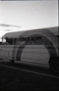 Thumbnail of Free Spirit Press crew hanging out the windows of their bus (blurry)
