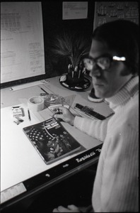 Thumbnail of Robinson Truitt, seated at a drafting table, looking at The New Soldier by John             Kerry and Vietnam Veterans Against the War