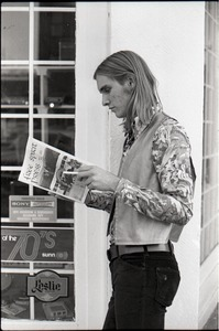Thumbnail of Tom Frank, standing on a corner, reading a copy of Free Spirit Press (vol.             1, 4)