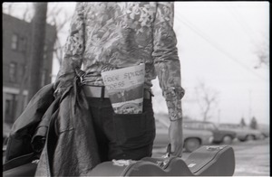 Thumbnail of Tom Frank walking away from the camera, carrying a guitar case and a copy of Free Spirit Press (vol. 1, 4) in his rear pocket