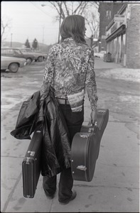 Thumbnail of Tom Frank walking away from the camera and             carrying a guitar case, a copy of Free Spirit Press (vol. 1, 4) in his rear pocket