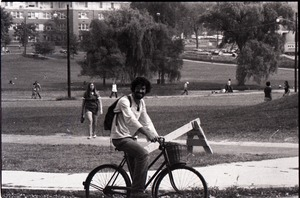 Thumbnail of Unidentified man riding bicycle on UMass Amherst campus: Campus Pond and Morrill         Hall in background
