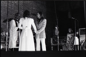 Thumbnail of Wedding of Jim and Anne Baker: exchanging vows in front of minister and drum set