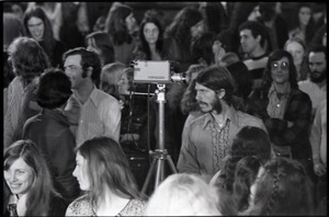 Thumbnail of Wedding of Jim and Anne Baker: Bruce Geisler with video camera standing among wedding guests