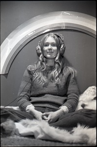 Thumbnail of Lynn Smith on a faux fur blanket, modeling Koss headphones