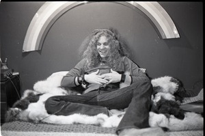 Thumbnail of Richie Miller, lying on faux fur blanket, modeling Koss headphones