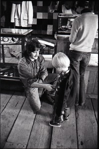 Thumbnail of Don Muller kneeling fit a child with a belt, the Leather Shed