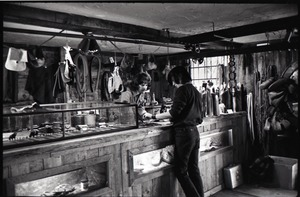 Thumbnail of Don Muller behind the counter with a customer, the Leather Shed