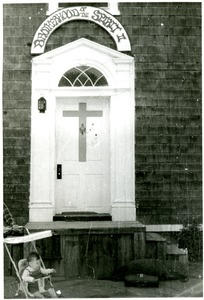 Thumbnail of View of the doorway (with sign) to a Brotherhood of the Spirit         house on Main Street