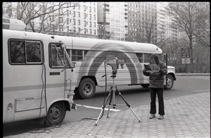 Thumbnail of Richard Safft reading copy of Free Spirit Press, standing by camera and Free             Spirit Press bus, during interview by Channel 5 news
