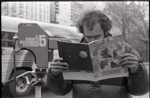 Thumbnail of Richard Safft reading copy of Free Spirit Press magazine during interview by Channel 5 news