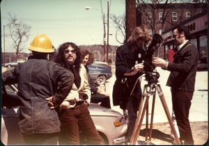 Thumbnail of Michael Metelica helping to set up a shot with the video camera outside in             Turners Falls