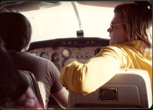 Thumbnail of Jim Baker flying in the co-pilot's seat of the commune's Cessna