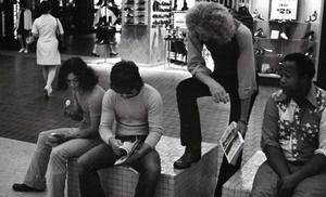 Thumbnail of Commune member distributing Free Spirit Press in an indoor shopping mall:             communard with group seated in center of the mall
