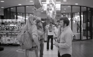 Thumbnail of Commune member distributing Free Spirit Press in an indoor shopping mall:             self-portrait of photographer photographing a group talking about the magazine