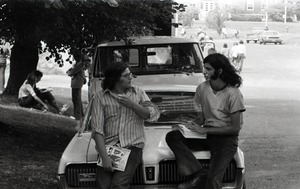 Thumbnail of Bill Grabin, with pile of Free Spirit Press magazine, talking with UMass Amherst student             sitting on the hood of a 1968 Mercury Cougar