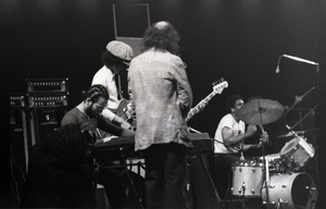 Thumbnail of Miles Davis in performance: Cedric Lawson (keyboard), Reggie Lucas (guitar), Dave Liebman (back             to camera), Al Foster (drums)