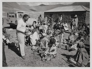 Thumbnail of Man addressing a group of villagers, seated in front of their huts