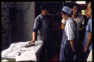 Thumbnail of Shanghai tractor building factory: workers in discussion by set of blueprints
