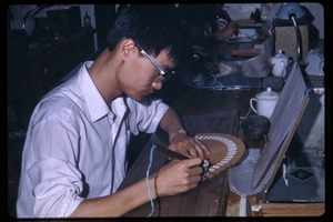 Thumbnail of Man at work, assembling a fan