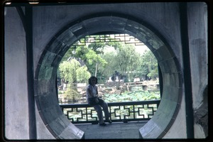 Thumbnail of Woman seated in garden setting, seen through circular archway (probably at Tiger Hill Pagoda)