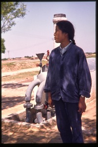 Thumbnail of Woman standing by pump