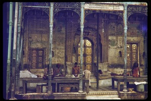 Thumbnail of Men, including a sadhu, seated and lying by gilded doors