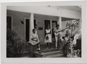 Thumbnail of White civil rights worker playing guitar on the front steps of the Freedom House         (Kathy Dahl, far right)