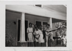 Thumbnail of White civil rights worker playing guitar on the front steps of the Freedom House         (Marjorie Merrill, 2d from left)