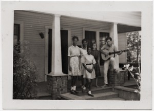 Thumbnail of White civil rights worker playing guitar on the front steps of the Freedom House         (Kathy Dahl, 2d from right)