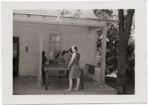 Thumbnail of Marjorie Merrill playing ping pong with children on porch of Rust Avenue             house rented by the Congress of Federated Organizations (COFO)