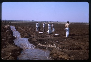 Thumbnail of Men walking next to a irrigation ditch