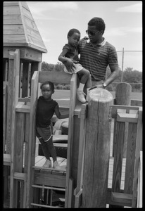 Thumbnail of Rory McClaurin with children atop playground equipment