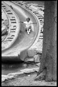 Thumbnail of Child descending a slide at a playground