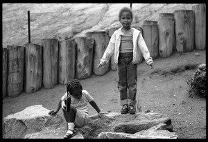 Thumbnail of Children playing on large rocks in a playground