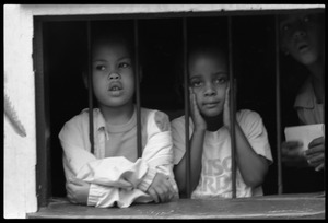 Thumbnail of Girls looking out a barred window