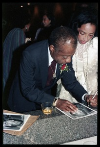 Thumbnail of James Baldwin autographing a photo for Onita Estes-Hicks at his 60th birthday celebration, UMass             Campus Center