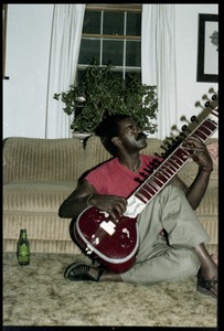 Thumbnail of Bobby Davis (?) playing a sitar in a living room floor