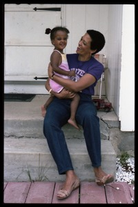 Thumbnail of Johnnetta Cole seated on the front steps of a house, holding Zena Allen