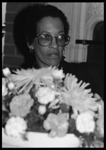 Thumbnail of Johnnetta Cole seated behind a basket of flowers at the 10th anniversary celebrations for Women's Studies at UMass Amherst