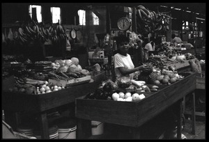 Thumbnail of Woman operating a market stall in the old marketplace, selling fruit, Belize City