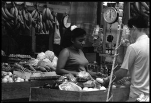 Thumbnail of Woman selling produce from a market stall in the old marketplace, Belize City