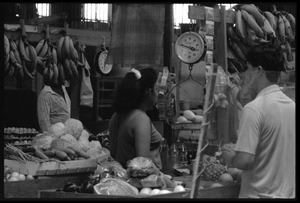 Thumbnail of Woman behind the counter at a market stall selling produce in the old marketplace, Belize City